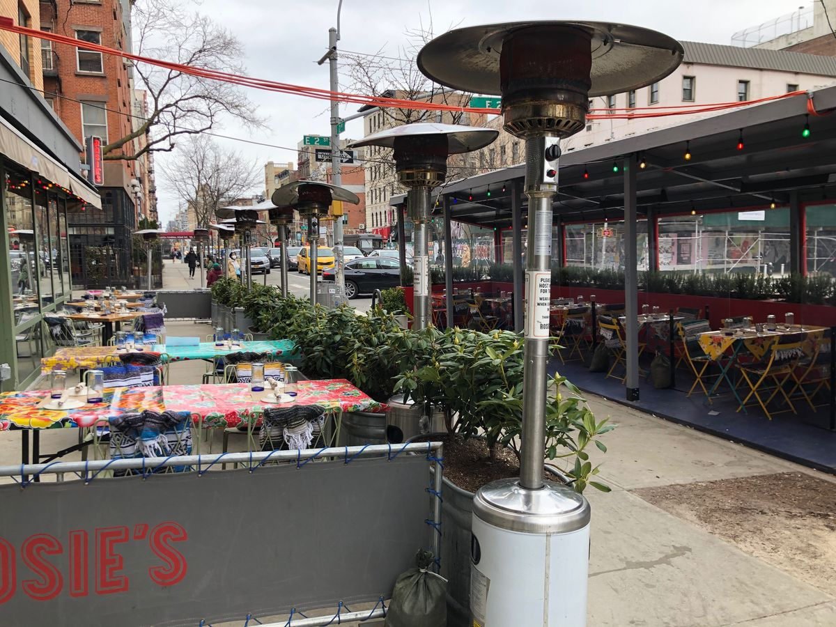 Outdoor seating with propane gas heaters set up near tables and chairs on the sidewalk
