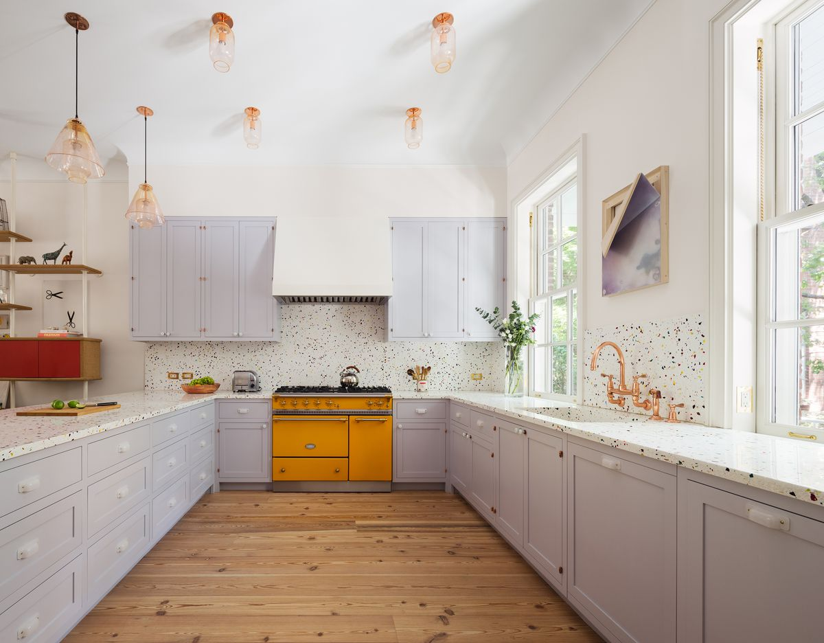 A kitchen. The cabinetry is light grey. There is a hardwood floor. There is a bright yellow oven. There is artwork hanging above the sink. There are light fixtures hanging from the ceiling.