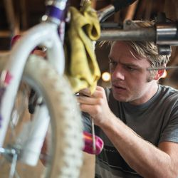 A man works on a child's bike at the Provo Bicycle Collective.
