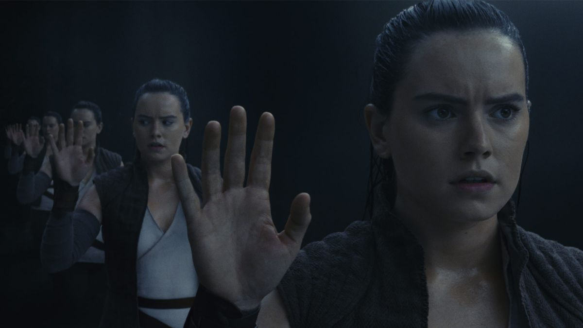 Rey standing inside the cave below Ach-To, images of herself repeating into the distance.