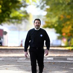 The Rev. Salvatore Sapienza walks on the quiet street outside of the Douglas Congregational United Church of Christ in the village of Douglas, Mich., on Tuesday Oct. 13, 2020. As part of the Our Faith Our Vote 2020 initiative, volunteers at the church will drive voters with their completed mail-in ballots to the county clerk's office to drop them off in person. The drivers and voters will be masked and separated in vehicles to minimize any COVID-19 risk.