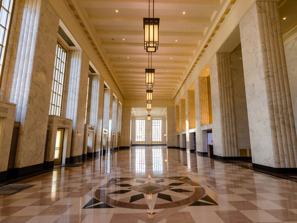 A long space with high ceilings, polished stone floors, tall windows, and rectangular chandeliers.