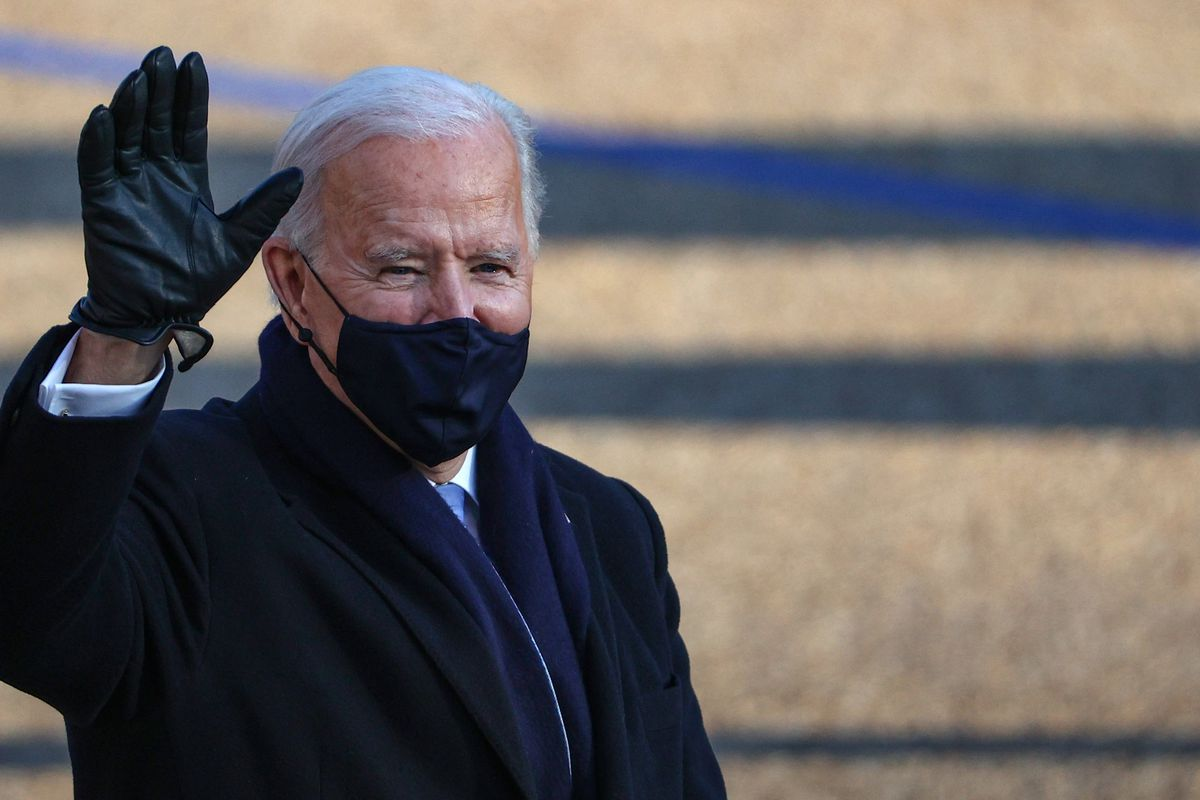 Biden waves while wearing a mask.