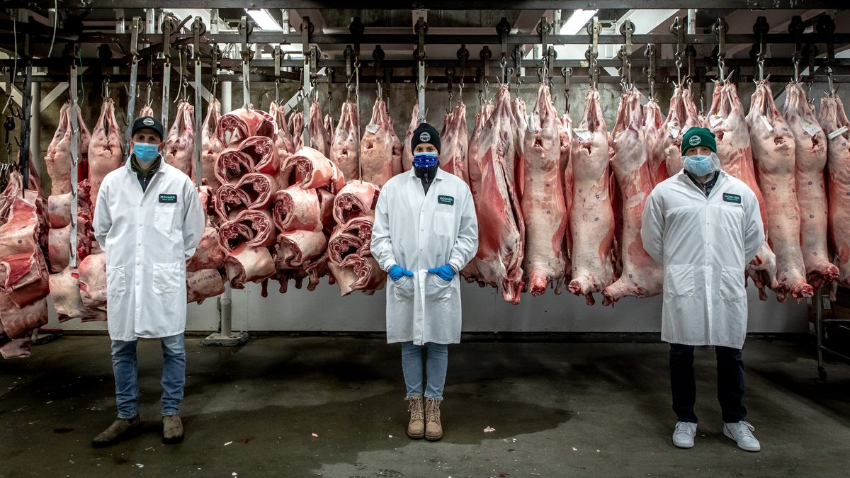 Seth, Jessica, and Ben Mosner stand apart from each other in a walk-in freezer with hanging meat