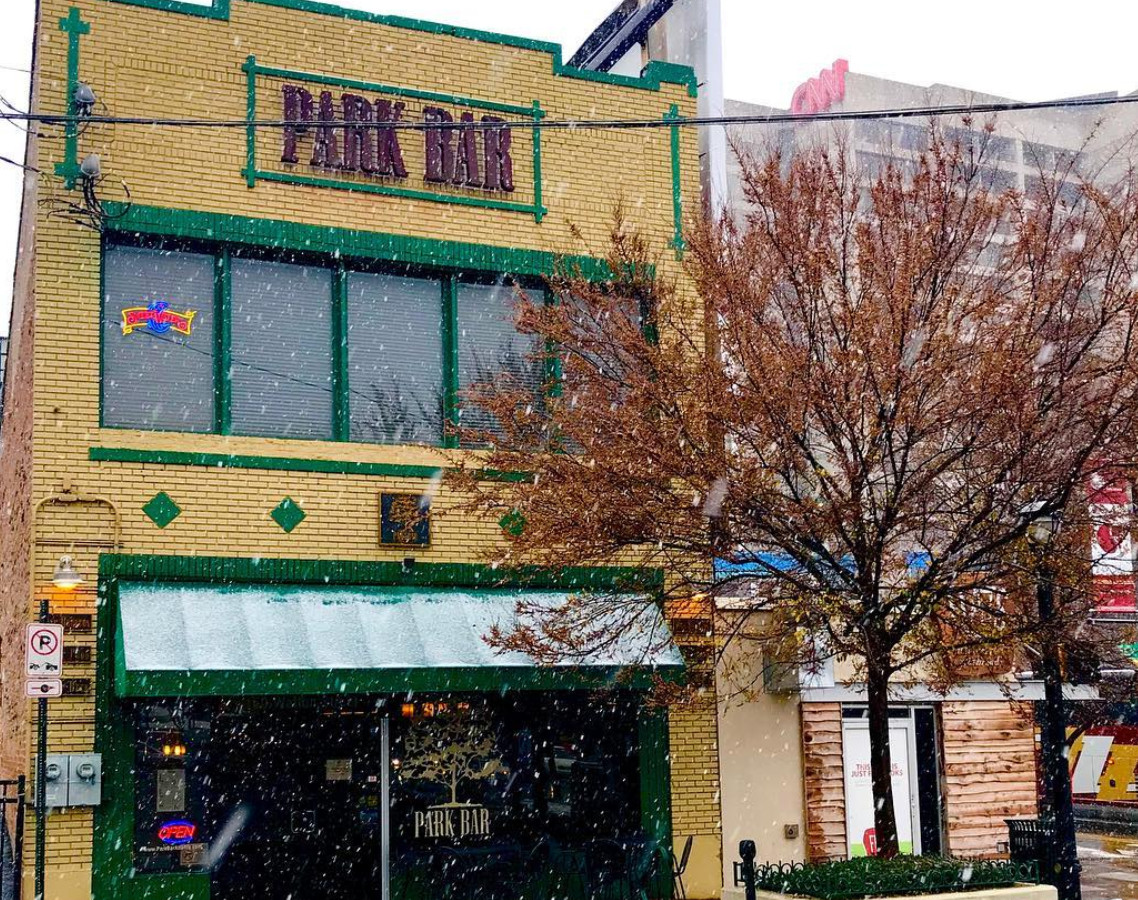 The exterior of a bar. The building facade is yellow and there is a sign on the building that reads: Park Bar. There is a tree in front of the building. It is snowing.