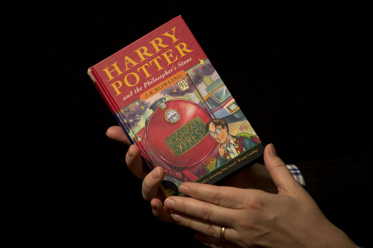"""Sotheby's director of the department of printed books and manuscripts Dr Philip Errington poses for photographers with a first edition copy of the first Harry Potter book """"Harry Potter and the Philosopher's Stone"""" containing annotations and illustrations"""