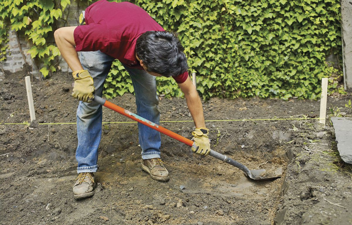Man Using Spade To Dig Topsoil For Bluestone Patio