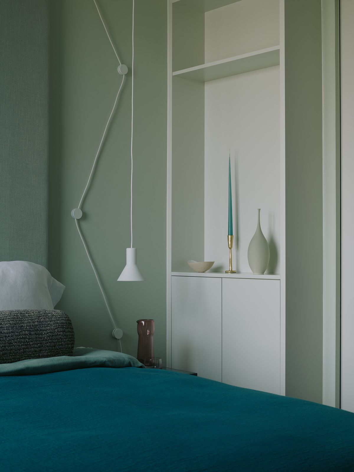 A bed with blue covers next to a white shelf.