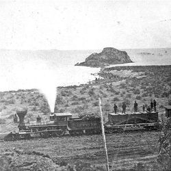 The engine Jupiter of the recently completed transcontinental railroad pulls a train near the shores of the Great Salt Lake after 1870.