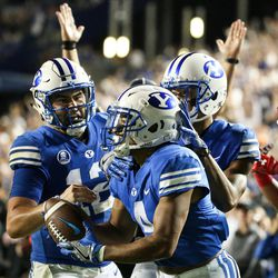 Brigham Young Cougars quarterback Tanner Mangum (12), running back Trey Dye (4) and wide receiver Micah Simon (13) celebrate after Dye scored a touchdown on a pass from Mangum, making the score 19-13 Utah, at LaVell Edwards Stadium in Provo on Saturday, Sept. 9, 2017.