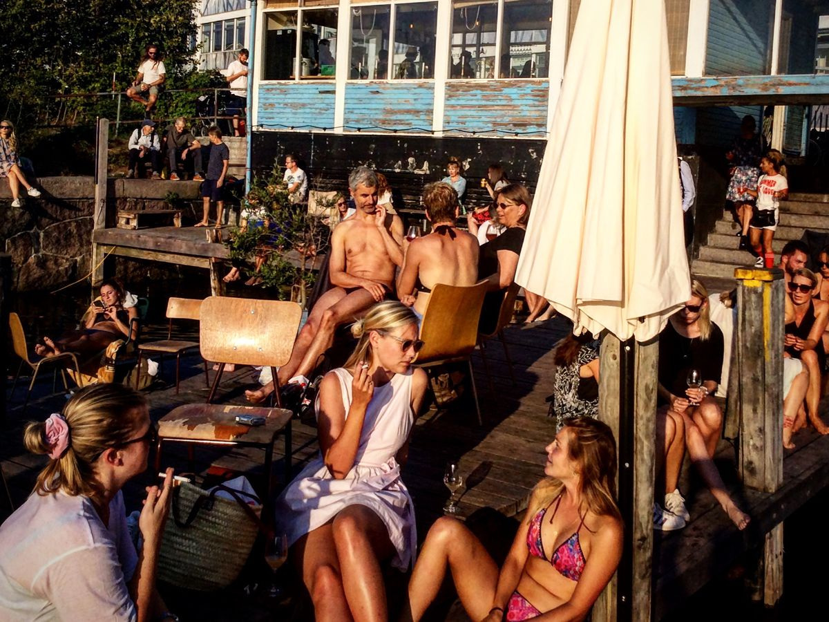 A crowd of people sit with drinks on a dock outside a restaurant, some of them sunbathing