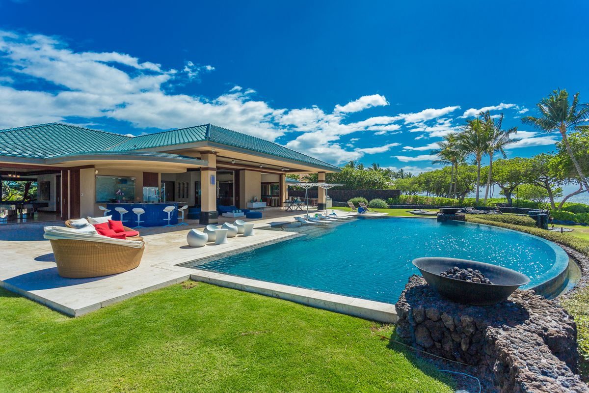 An exterior view of a single story home in Hawaii. The home has a pool in front and a teal tiled roof.