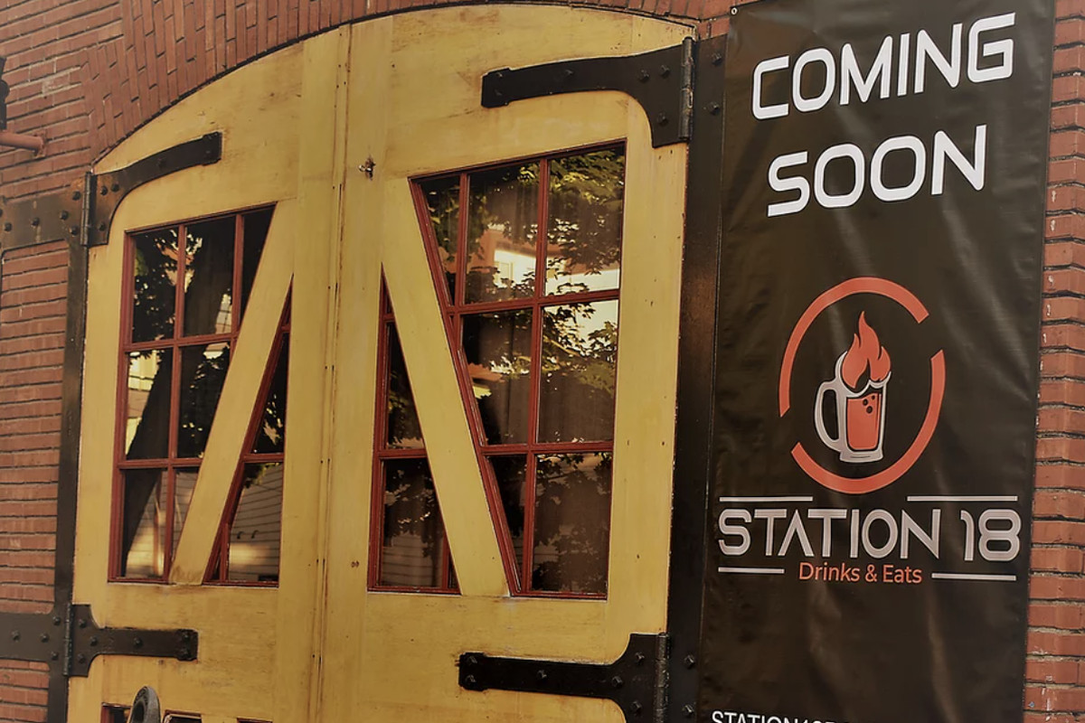 """The front of Station 18 Drinks and Eats, with a """"coming soon"""" banner on the side of the brick building"""