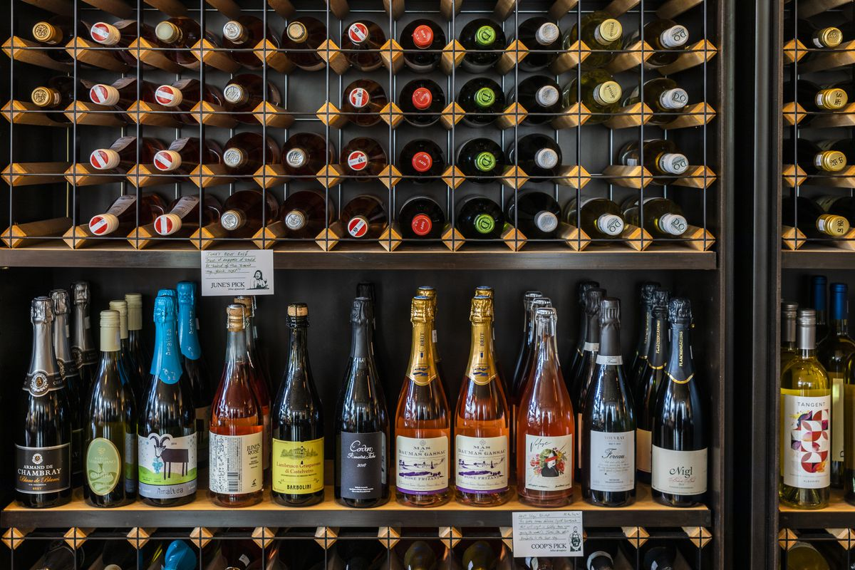 Rượu vang hồng và rượu vang đựng trong chai thủy tinh sẫm màu xếp chồng lên nhau trên kệ.  Bên trên chúng, rượu vang đặt bên cạnh chúng cũng được xếp trong các giá treo bằng dây.