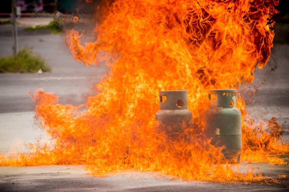 A stock photo of a huge fire surrounding two white propane tanks on a street.
