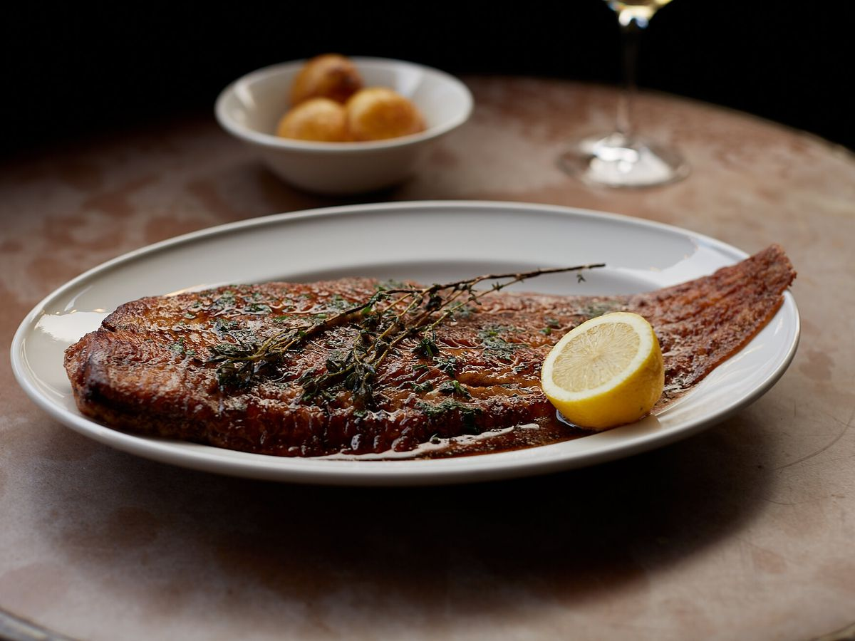 A large cut of steak on an oblong plate with thyme and lemon wedge for garnish, and a side dish blurred in the background on a wooden table