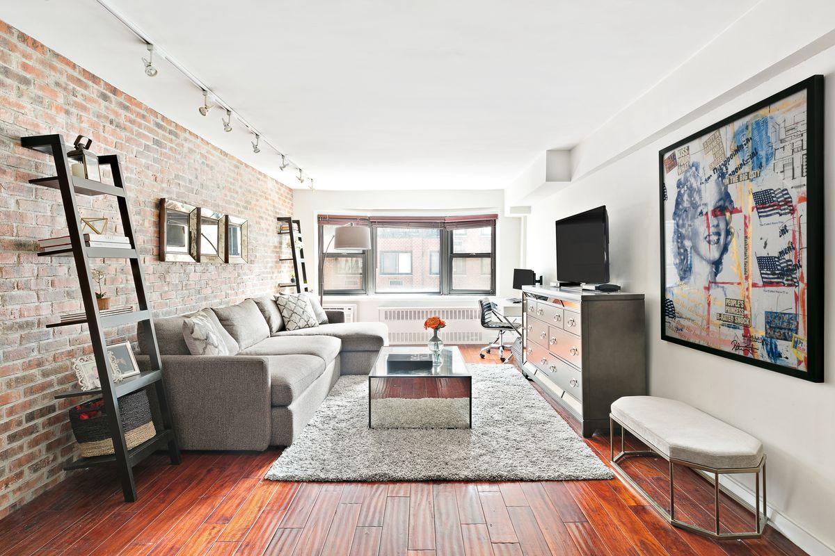 A living area with a grey couch, hardwood floors, exposed brick, and white walls.