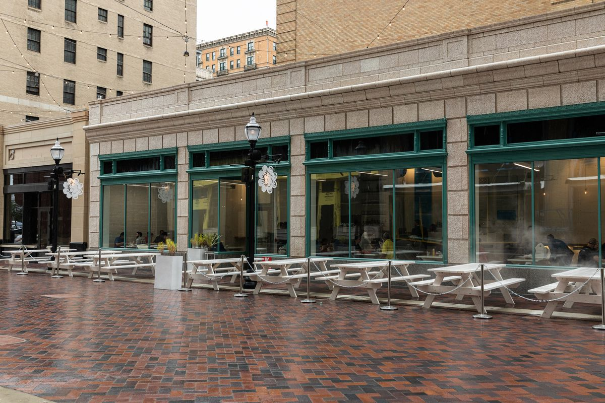 Frita Batidos's patio features white picnic tables roped off with a metal chain on a rainy day.