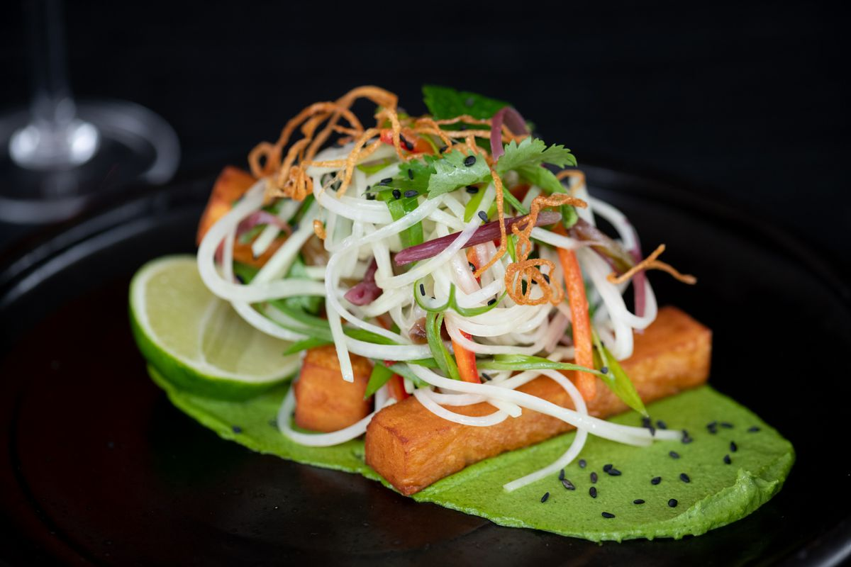 Two perfectly rectangular wedges of fried masa dough are stacked on top of a thick green sauce swiped on the black plate. On top are tenderils of rice noodles, micro cilantro, shaved carrot whisps and a smattering of black sesame seeds.