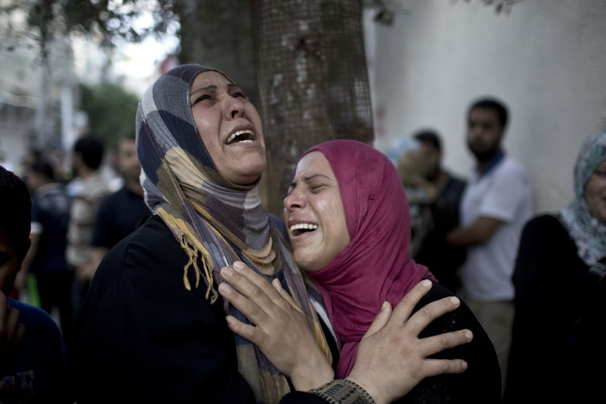 Palestinian women grieve over the death of relatives outside the morgue of the Kamal Adwan hospital in Beit Lahiya, on July 24, 2014, after a UN school in the northern Beit Hanoun district of the Gaza Strip was hit.