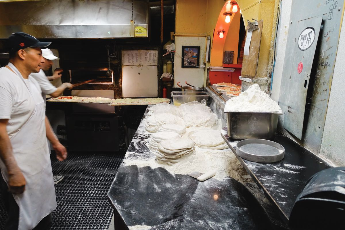 Employees stand in the Regina kitchen next to stacks of dough rounds and a big bin of flour