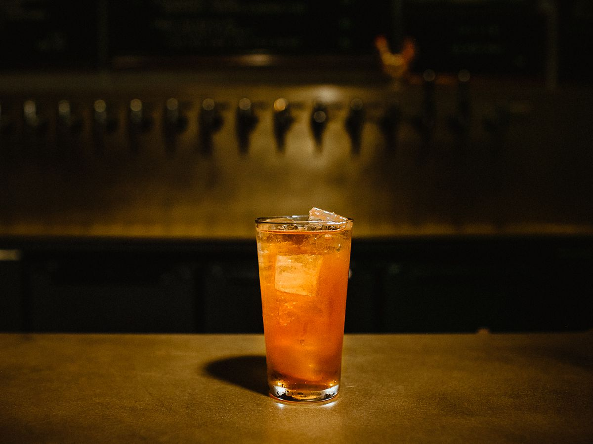 A lone orange cocktail sits on the counter of a bar, overflowing with ice but not liquid. In the background, a row of taps is visible.