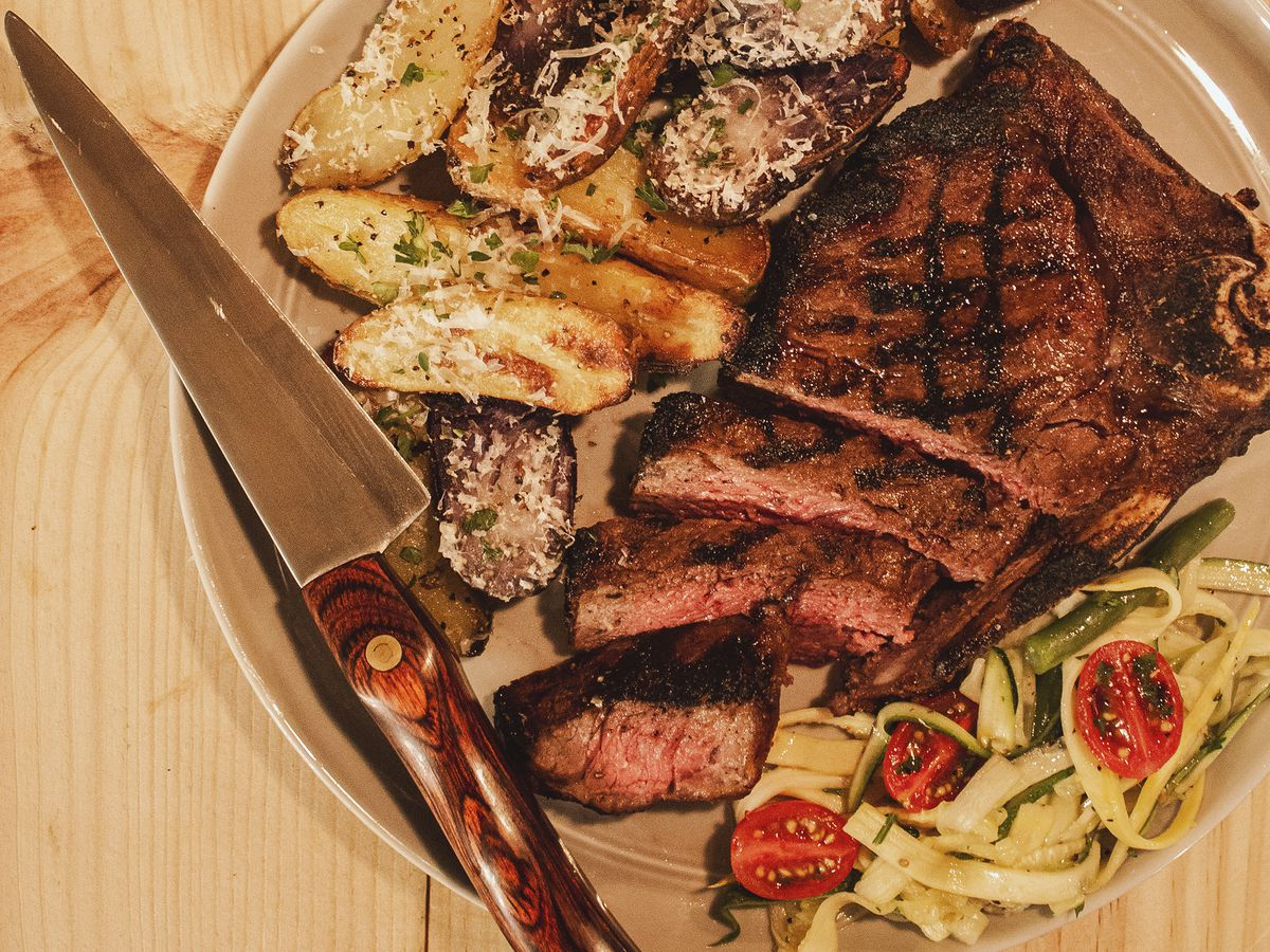 Sliced steak, cheesy potatoes, and zoodle salad, on a plate with a steak knife, on a wooden counter