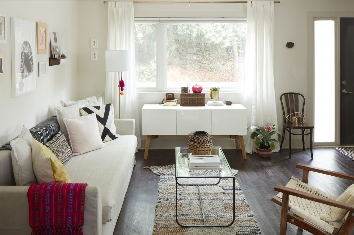 The living room is mostly white, with a light colored sofa, walls, and console.