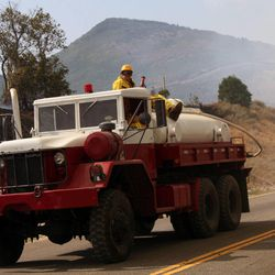 Firefighters work at the scene of a wild fire that is in both Wasatch County and Summit County near the Jordanelle Reservoir on Saturday, Aug. 18, 2012.