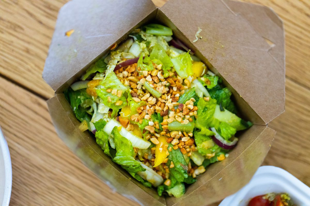 A cardboard box with salad in it.