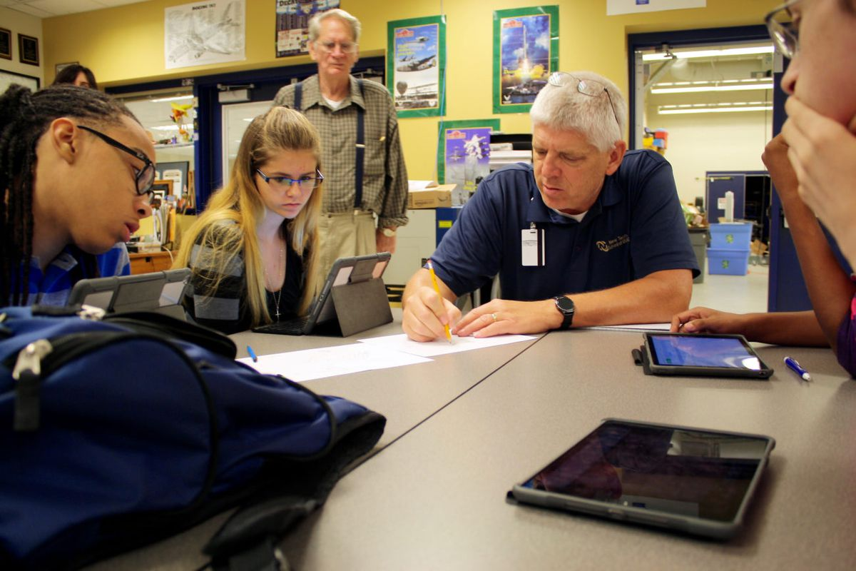 Students in Decatur Township work on physics problems with their teacher.