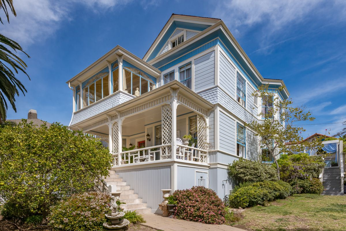 Wood-framed Victorian house with front porch and balcony sunroom.