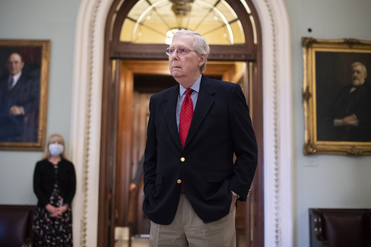 McConnell, in a navy jacket, tan slacks, and a red tie, stands with his hand in his pocket between two painted portraits.