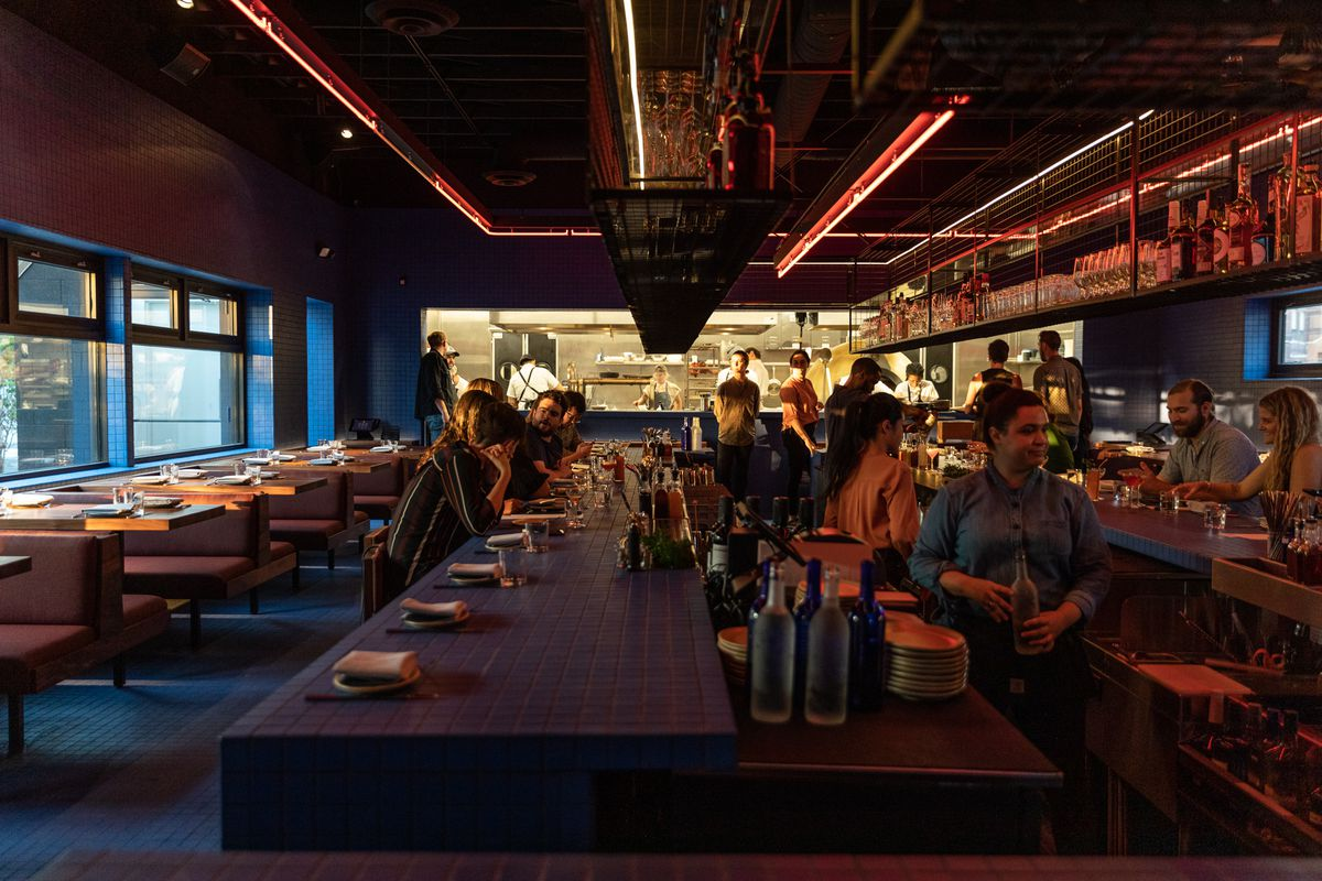 Customers are seated around the blue-tile bar at Magnet. Red lights around the ceiling cast a glow over the counter and the faces of patrons and bartenders.