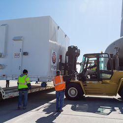 A forklift is used to move InSight's container onto the ground