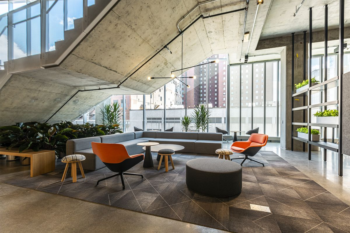 Tables and seating located below a concrete staircase and floor-to-ceiling glass walls.