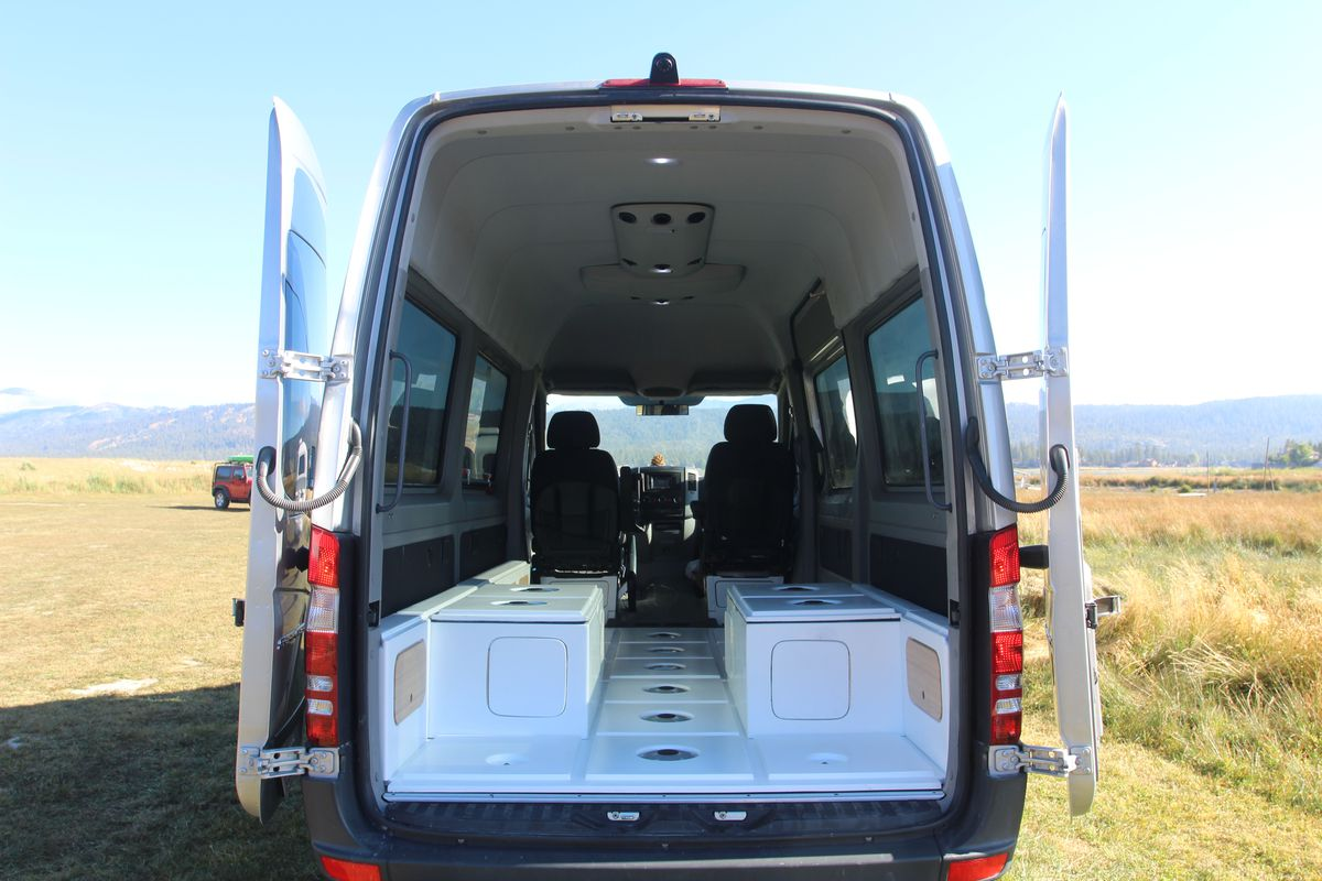 A photo of a silver Mercedes Sprinter with its rear doors open. Inside the van is a white fiberglass grid of cubes on the floor.