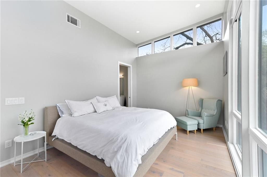 A large white and grey master bedroom with a white bed.