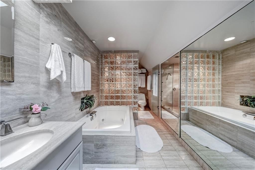 A long white and gray bathroom with glass blocks.