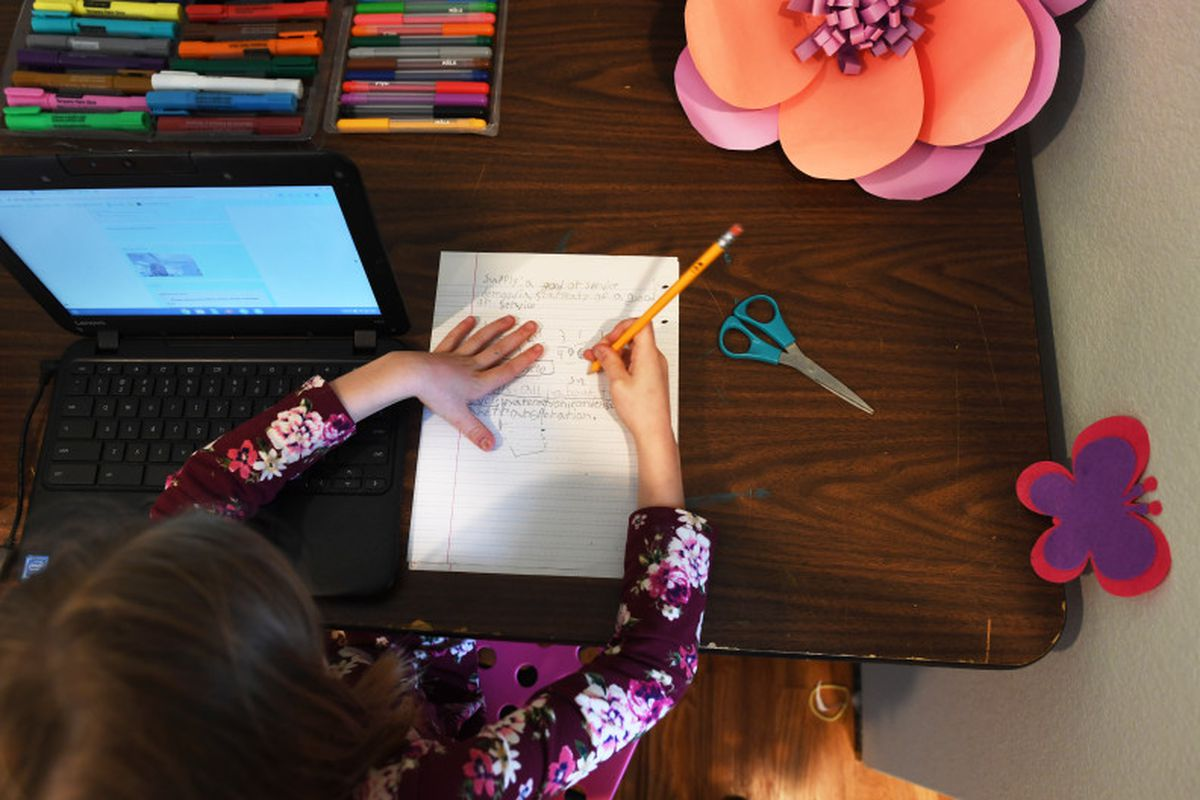 A girl wearing a colorful shirt works from her desk at home, writing on a piece of paper next to her laptop.