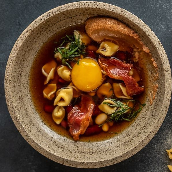 From above, a stone bowl filled with stew consisting of noodles, egg, chorizo, and a smear of beans