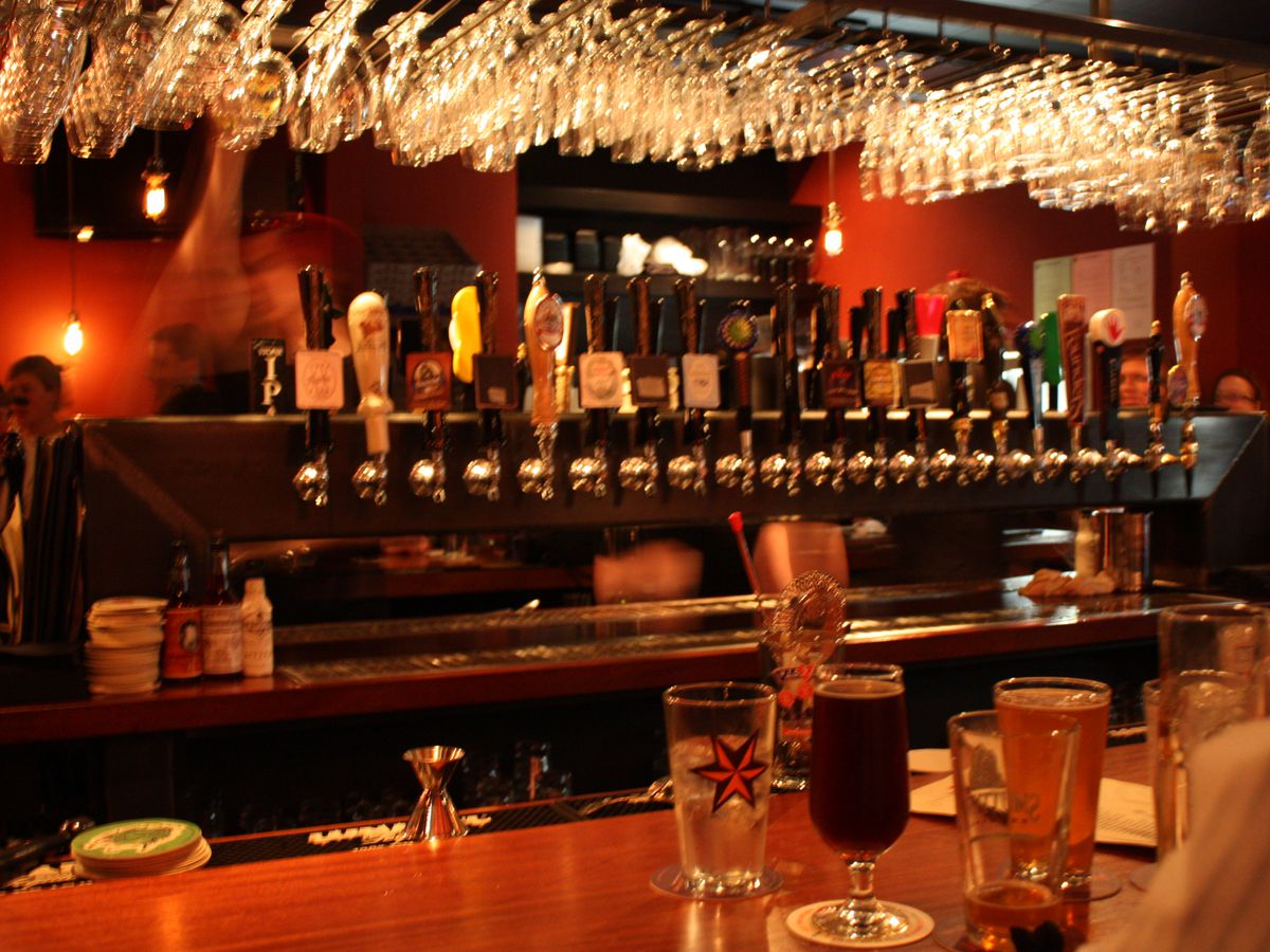 Slightly blurry shot of a dark bar interior with lots of red accents. A line of taps and hanging beer glasses are visible in the image.