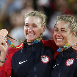 United States' Kerri Walsh Jennings, left, and April Ross, right, celebrate their bronze medals during an awarding ceremony for the women's beach volleyball event at the 2016 Summer Olympics in Rio de Janeiro, Brazil, Thursday, Aug. 18, 2016. (AP Photo/Petr David Josek)