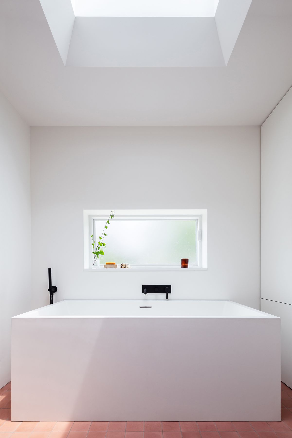 A white rectangular tub is surrounded by white walls and pink floors under a skylight.