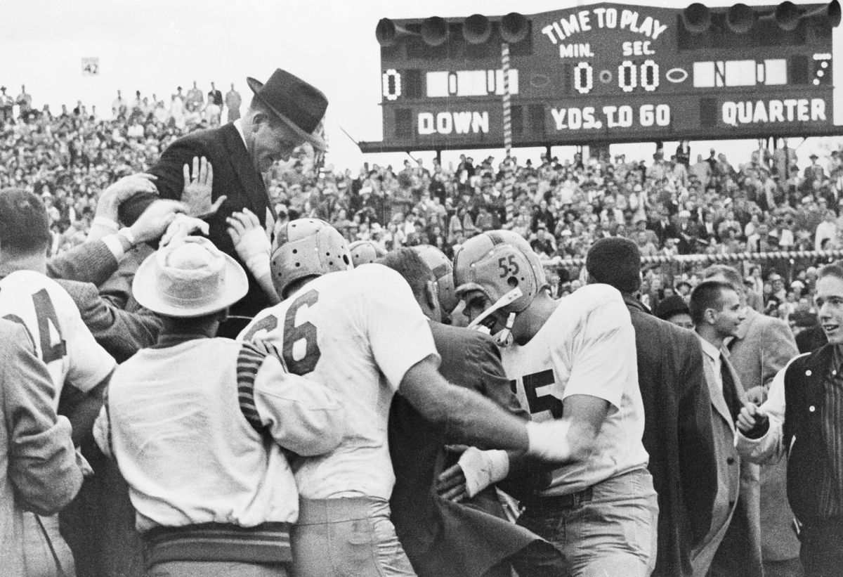 Victorious Notre Dame Football Players Carrying Coach