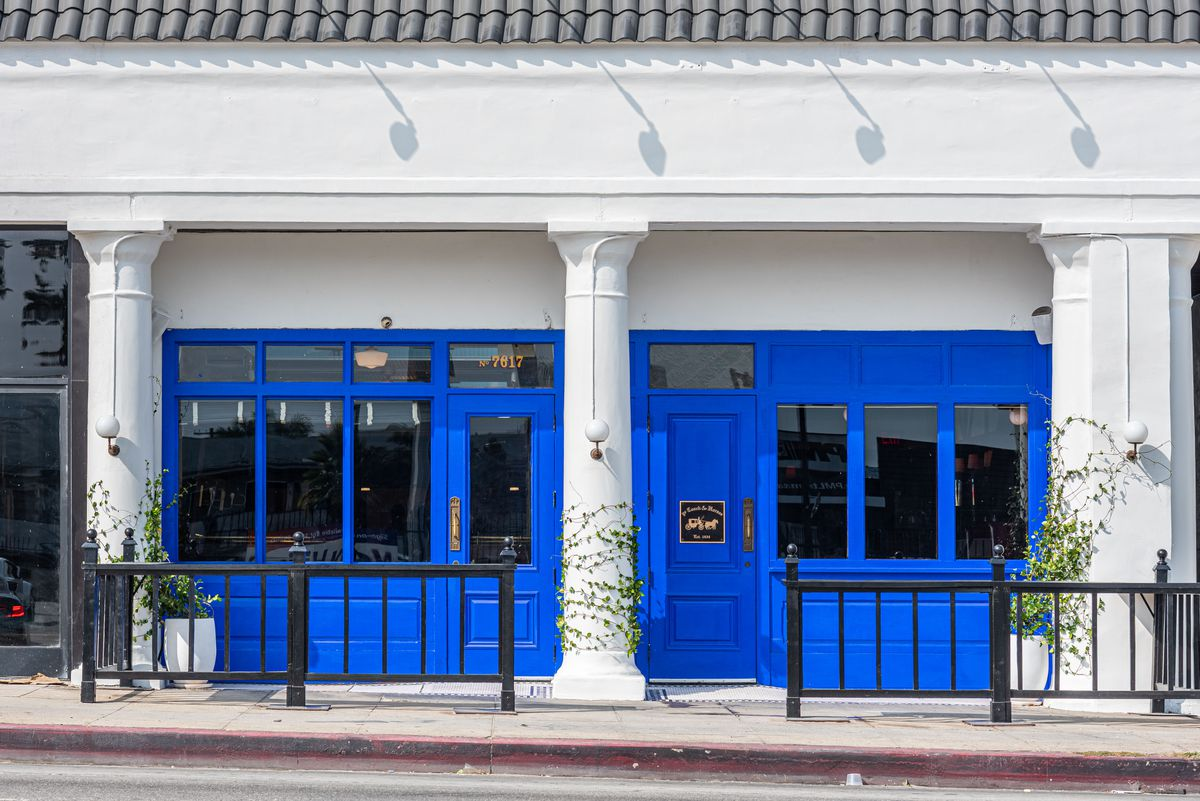 Bright blue doors and windows at a retro restaurant, shown during the day.