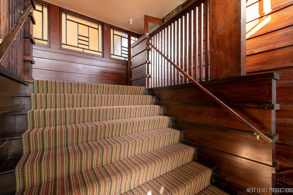 A wooden staircase with vertical slats and detailed trimwork. There is s striped carpet running up the center.