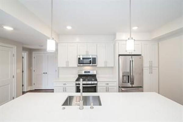 The view of a newer kitchen from over a granite countertop.