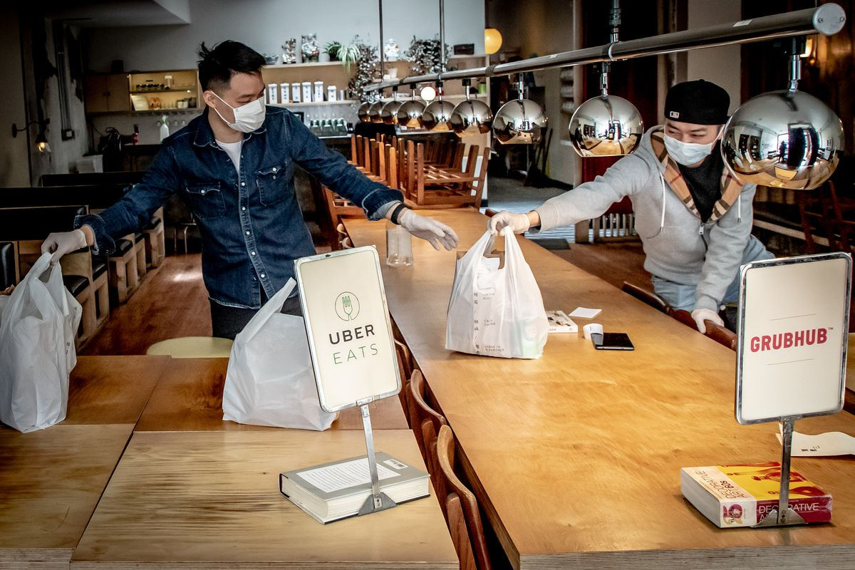 Workers at Birds of a Feather organize bags of orders by delivery service