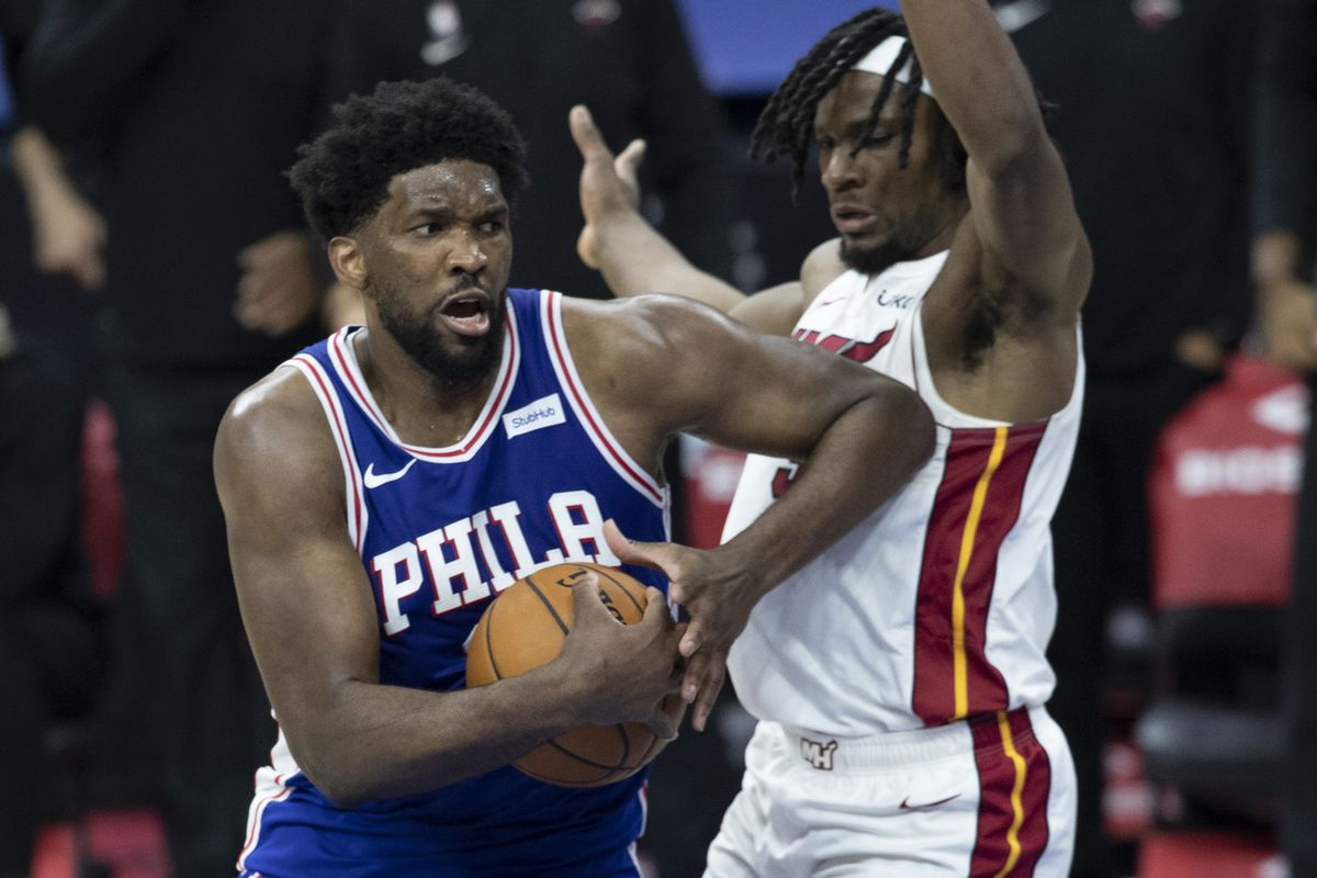 Joel Embiid of the Philadelphia 76ers drives to the basket against Precious Achiuwa of the Miami Heat in overtime at the Wells Fargo Center on January 12, 2021 in Philadelphia, Pennsylvania. The 76ers defeated the Heat 137-134.